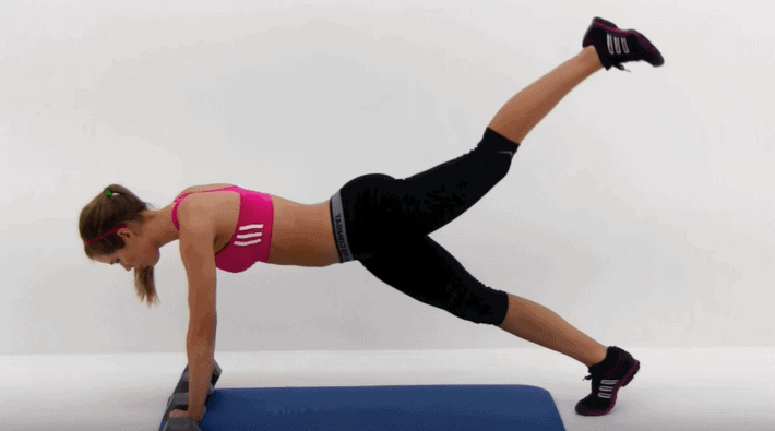 Woman planking while lifting one leg up