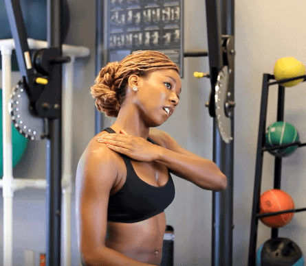 Woman touching her shoulder in a gym