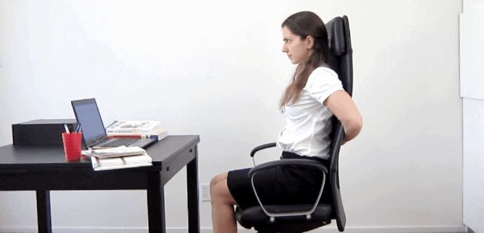 Woman doing back exercise in an office