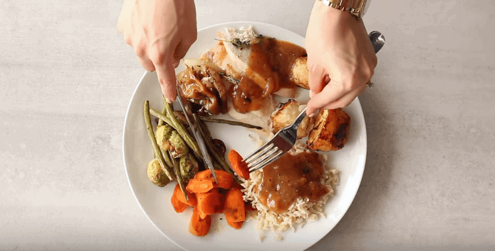 Person picking carrots from the plate with fork and knife