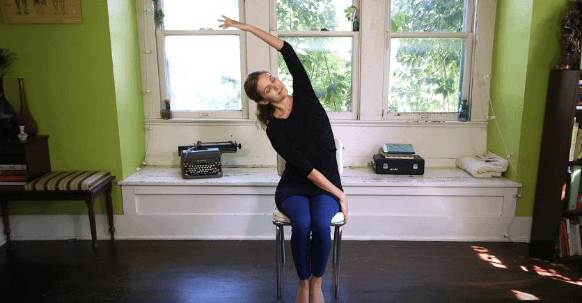 Woman stretching her back on a chair
