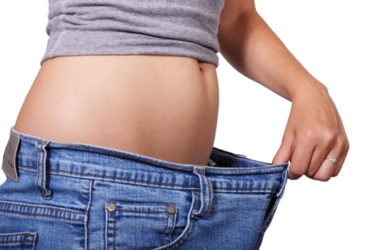 Woman wearing a pair of jeans too lose for her size