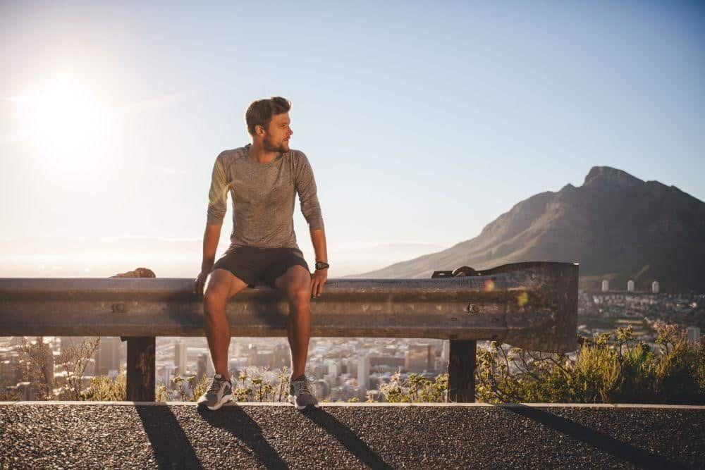 Man in fitness outfit sitting on a highway guardrail looking towards his left