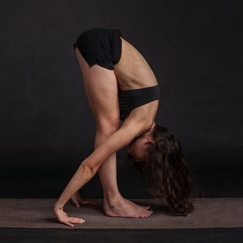 A woman stretching by folding herself into half