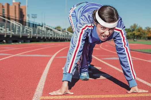 Person getting ready to run on a running track