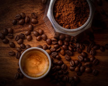 Top view of a cup of coffee, coffee powder and coffee beans
