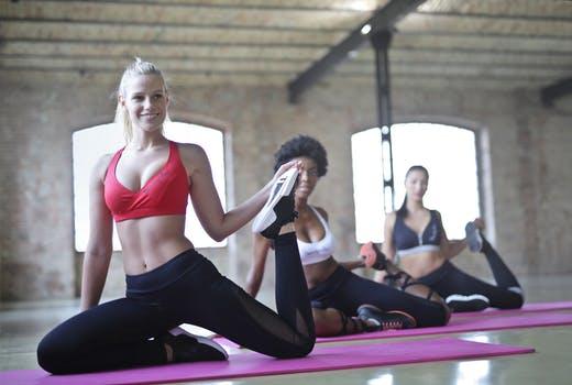 3 women stretching their legs in a gym