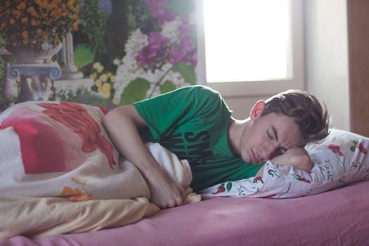 Teenage boy sleeping on a bed