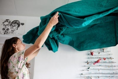 Woman tidying up the bed