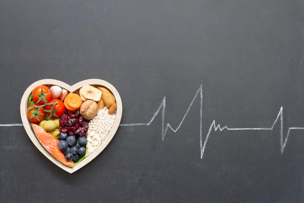 Heart shaped bowl with nutritious food on a blackboard with heartbeat line