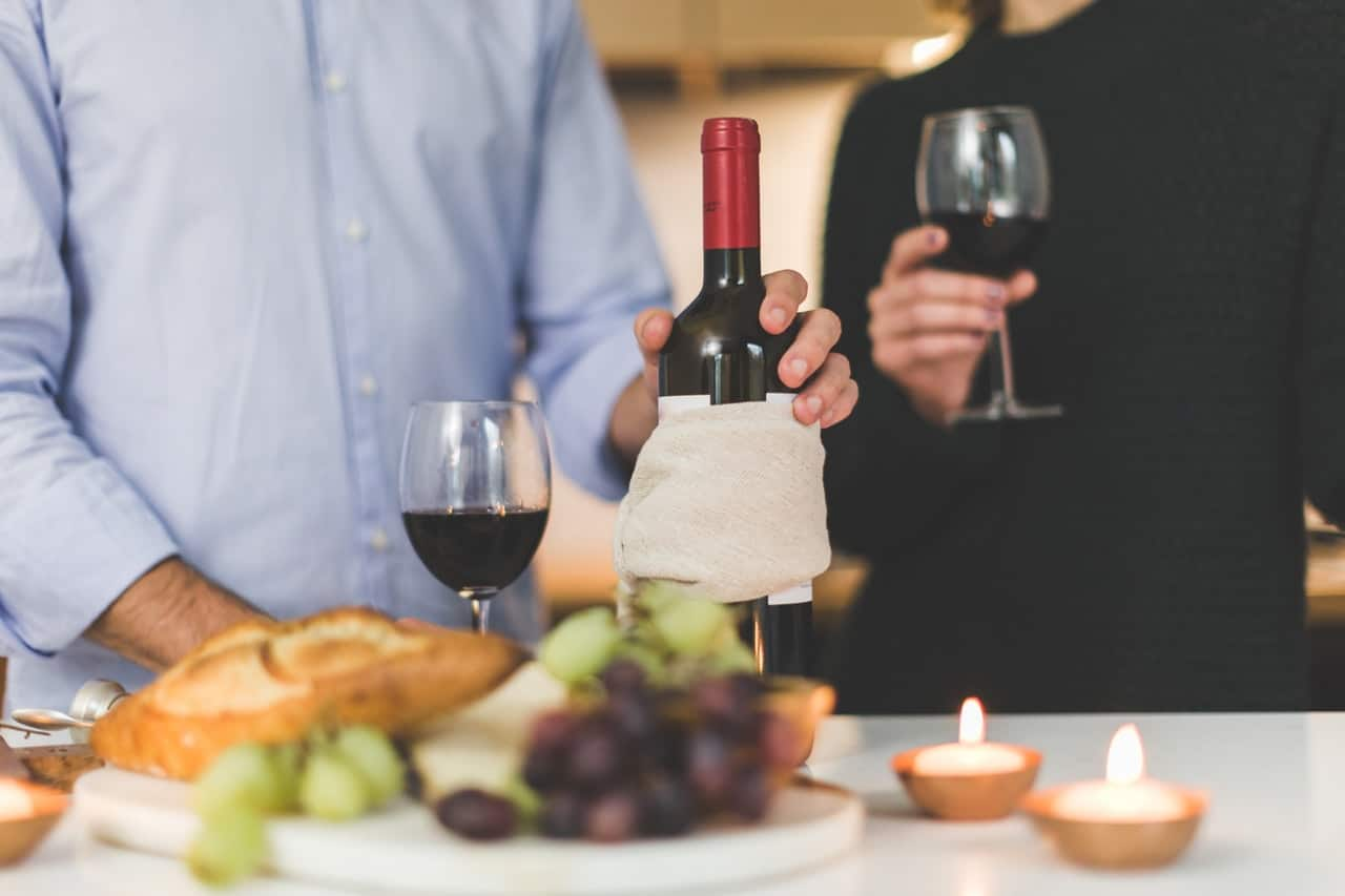 A man holding a bottle of wine while a woman holding a glass of wine