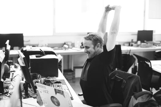 Man in office stretching while sitting