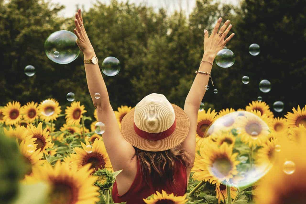 Back view of a woman surrounded by sunflowers and bubbles