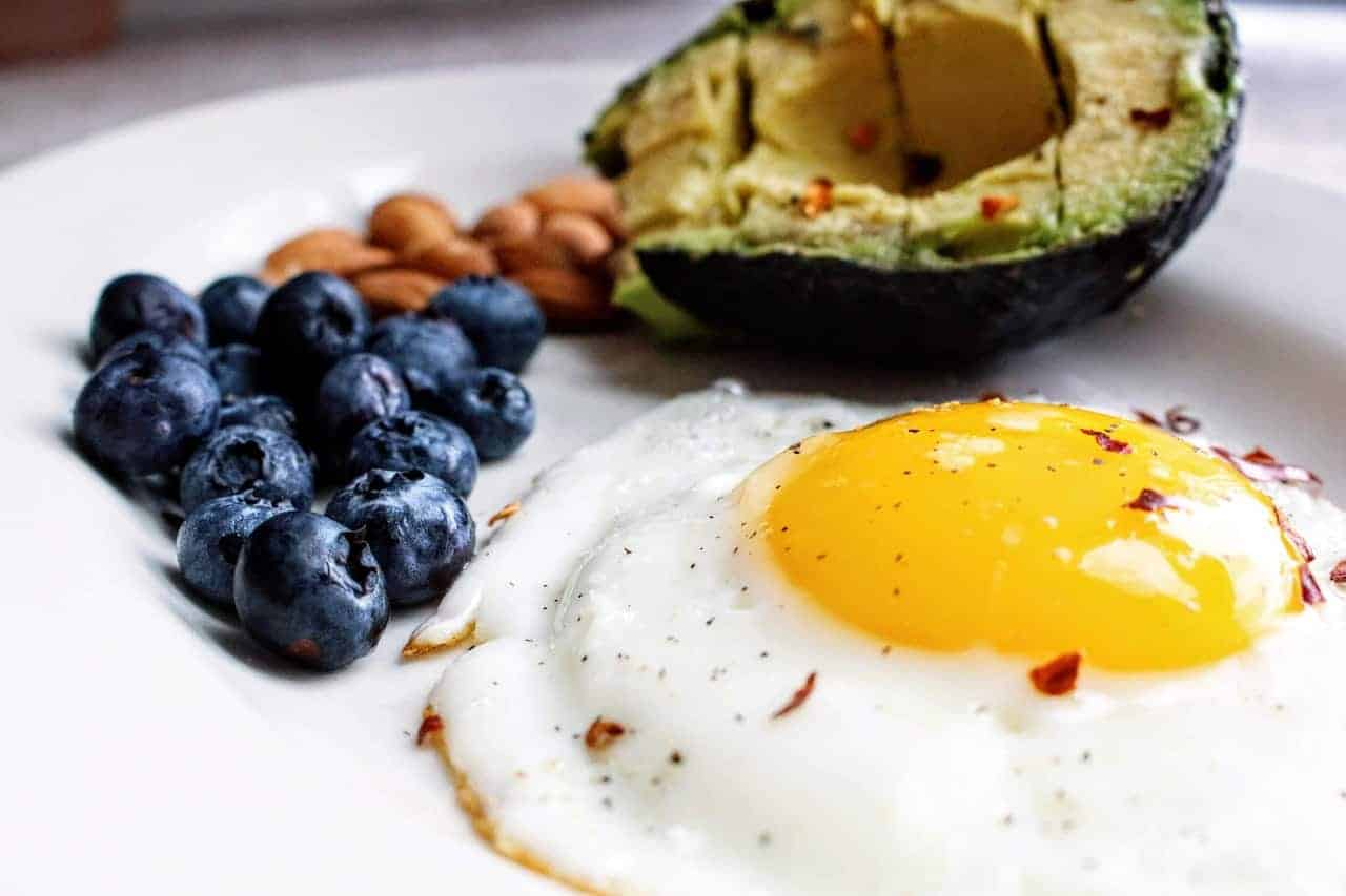 Fried egg, blueberries, almonds and avocado on a white plate
