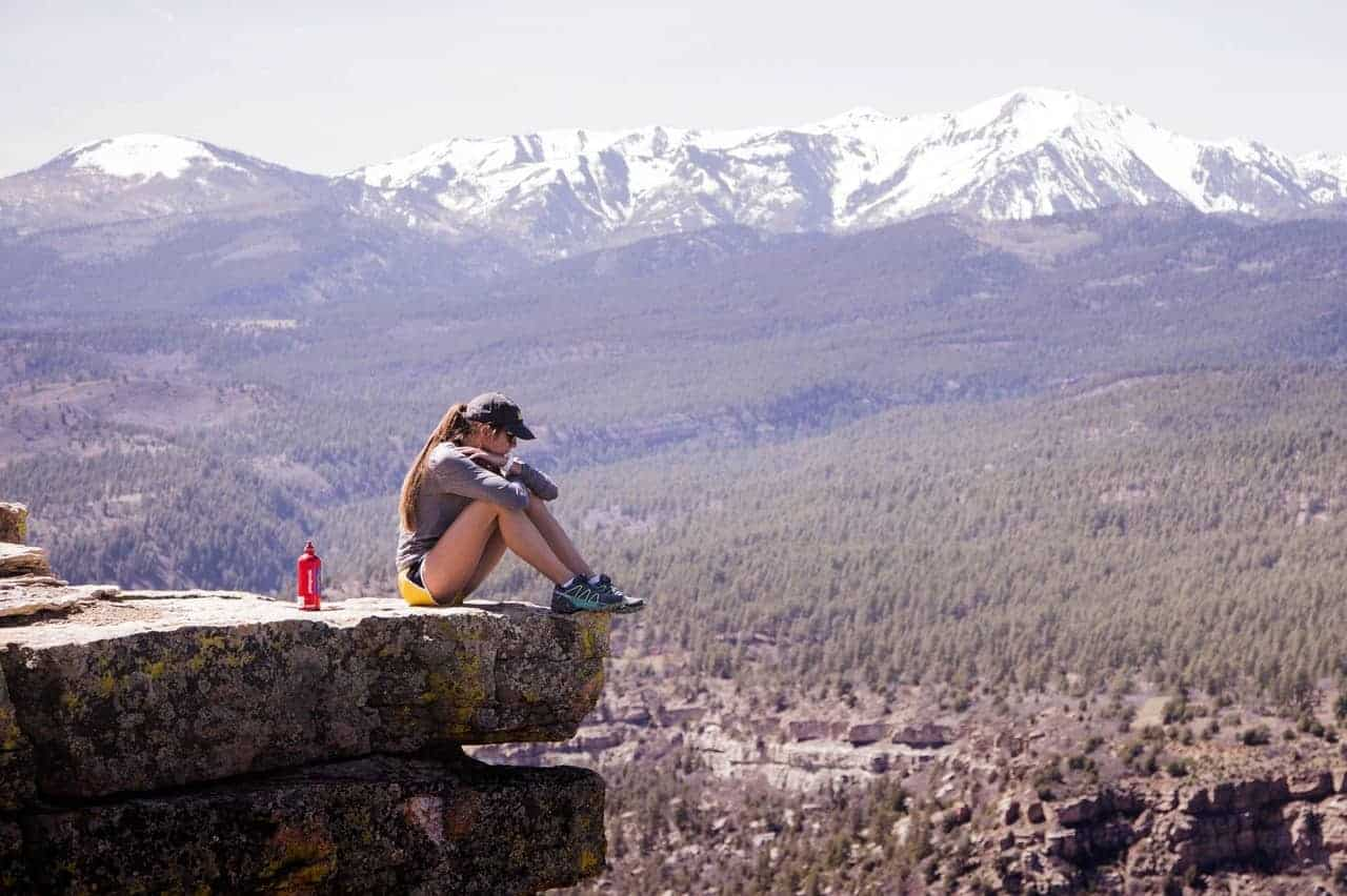 Woman sitting on the edge of a rock uphill