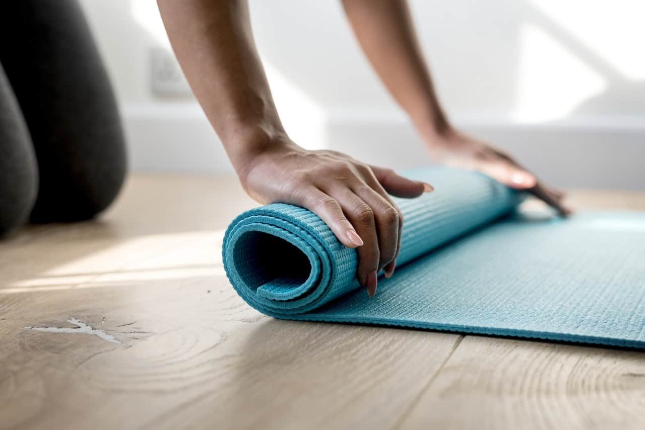Person rolling up a yoga mat