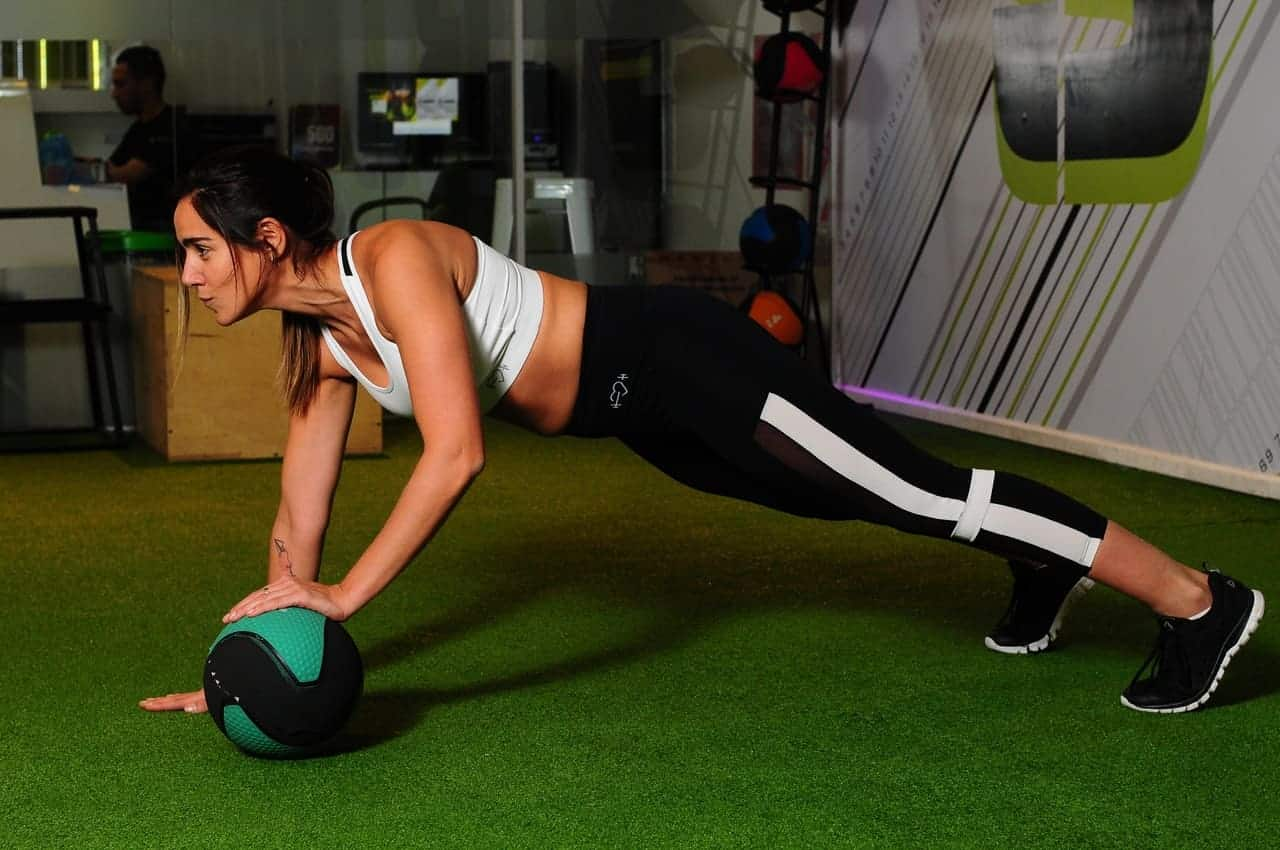 Woman planking while holding on to a medicine ball