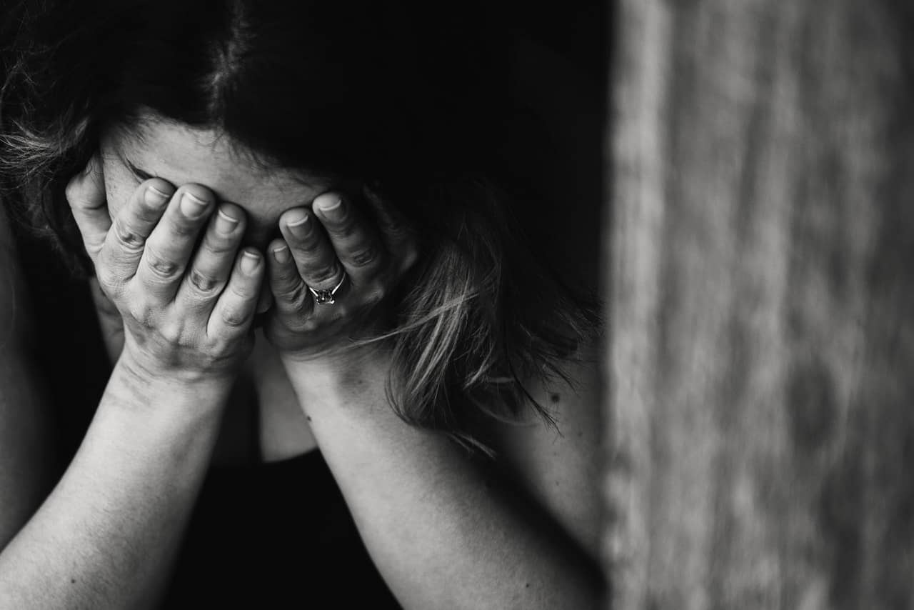 Black and white photo of a woman covering her face with her hands