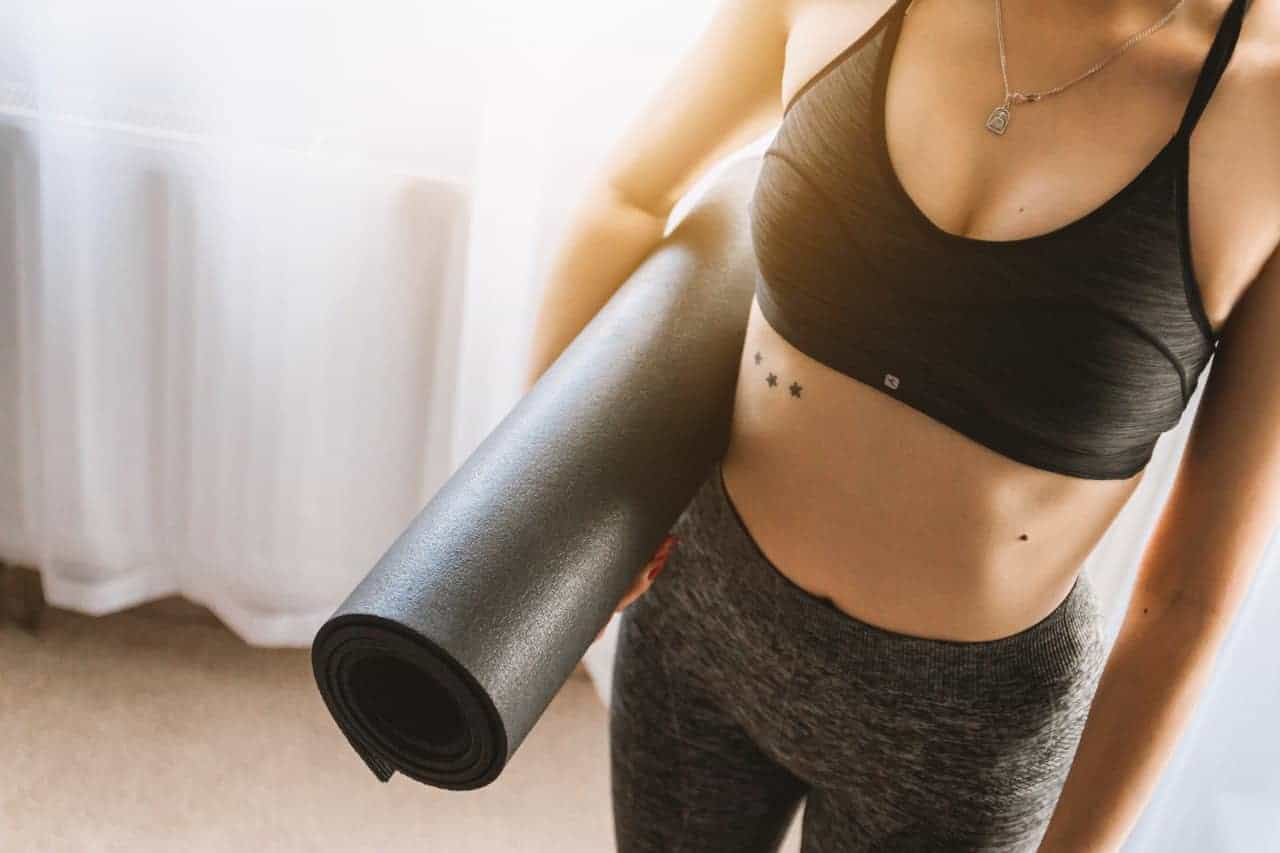 Woman holding a rolled up exercise mat