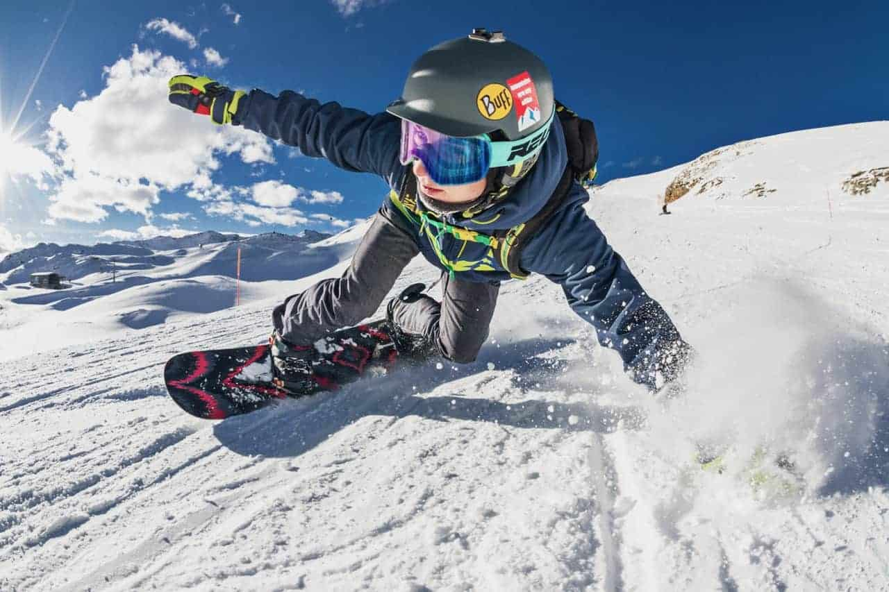 A snowboarder doing a cool move going down hill