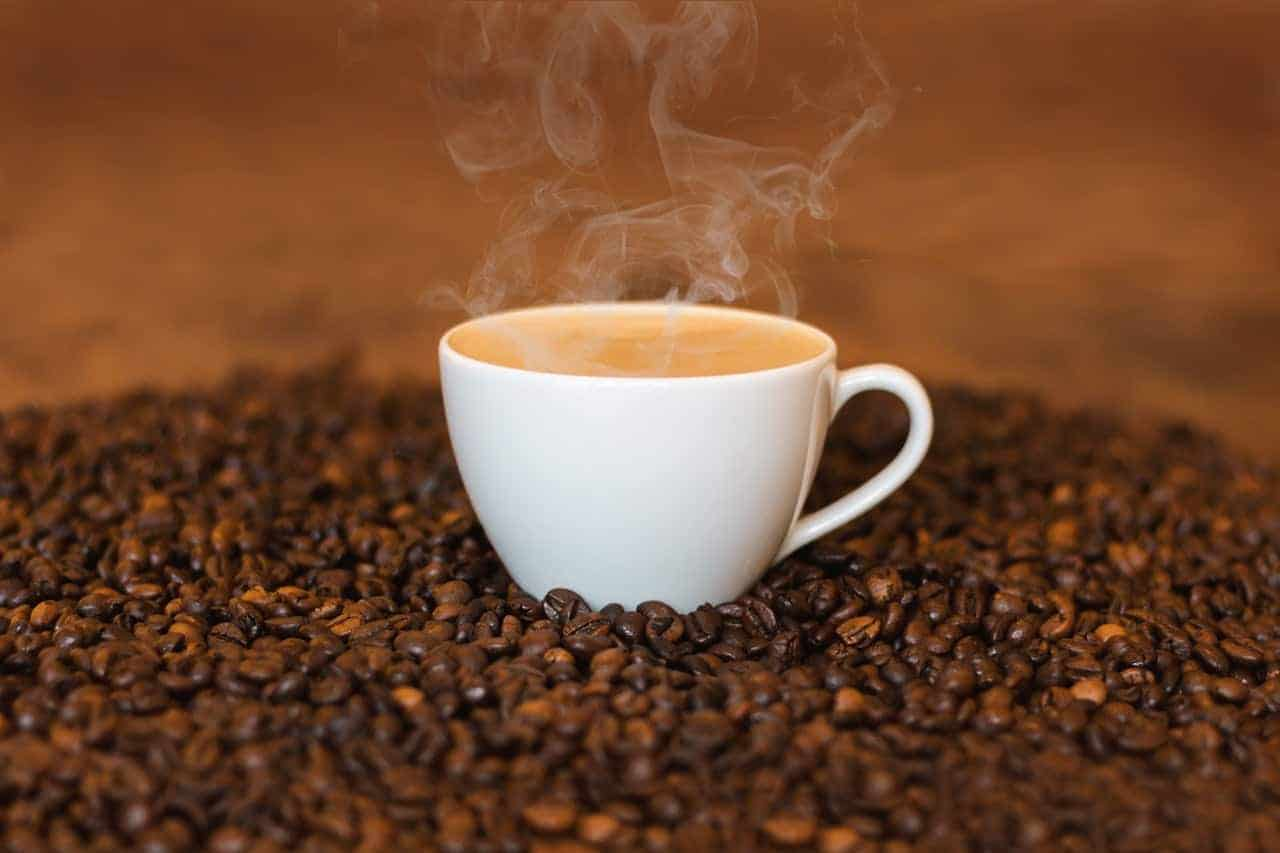 A cup of warm coffee on top of coffee beans