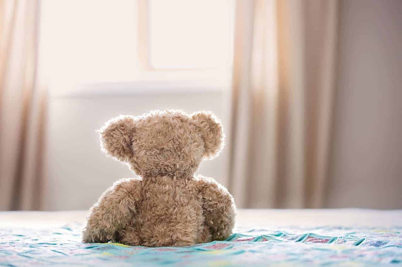 Back of a teddy bear sitting on a bed facing window