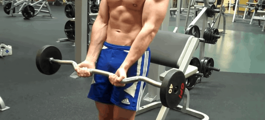 A man holding a curl up bar in a gym