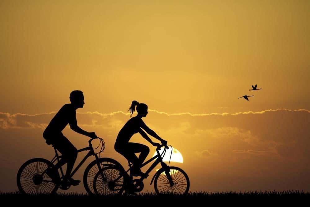 Silhouette of a couple riding bicycles over sunset