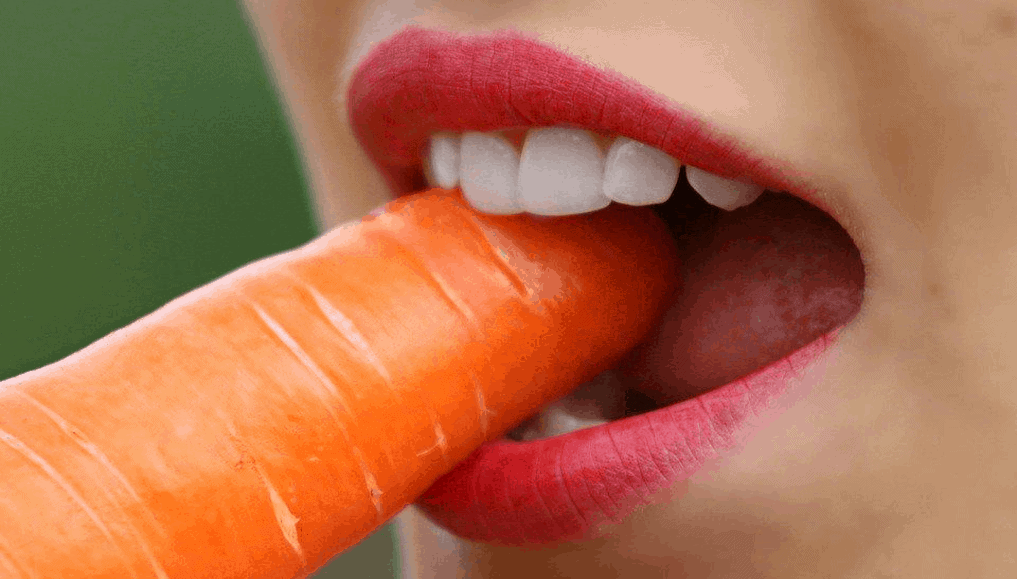 Close up shot of a woman biting into a carrot