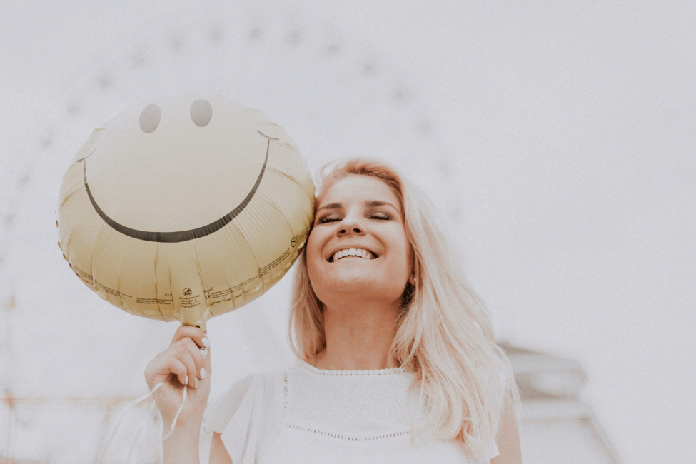 Smiling woman holding a smiley balloon