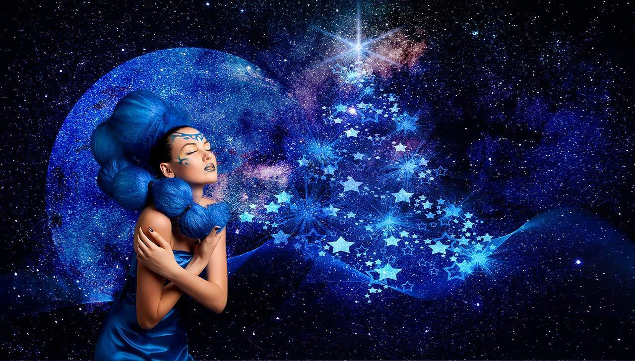 Woman with blue hair, makeup and dress with galaxy background and blue stars