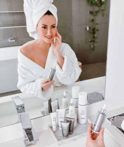 Woman holding a skincare product looking at herself in the mirror