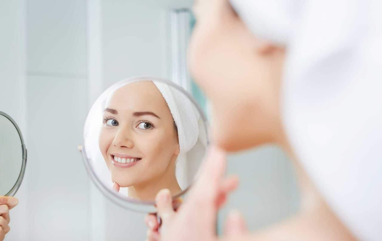 Smiling woman looking at herself in the mirror
