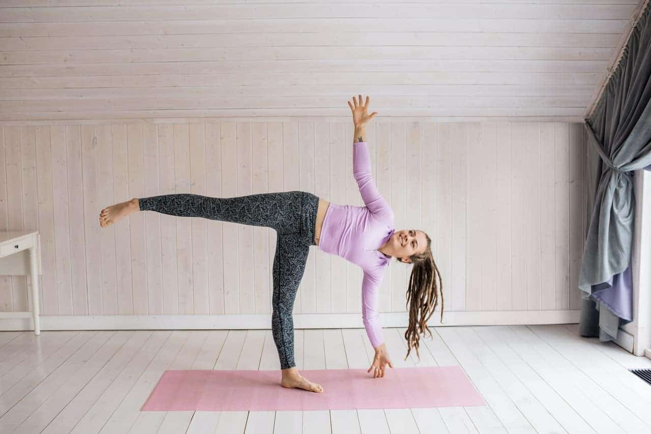 Woman balancing on one leg and one arm on the mat