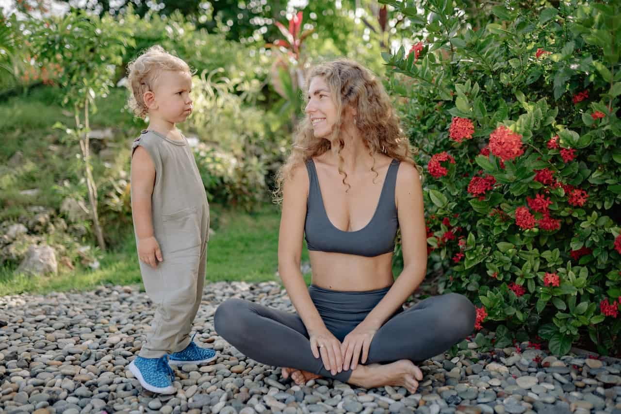 A woman in fitness gears sitting in a garden looking at a child