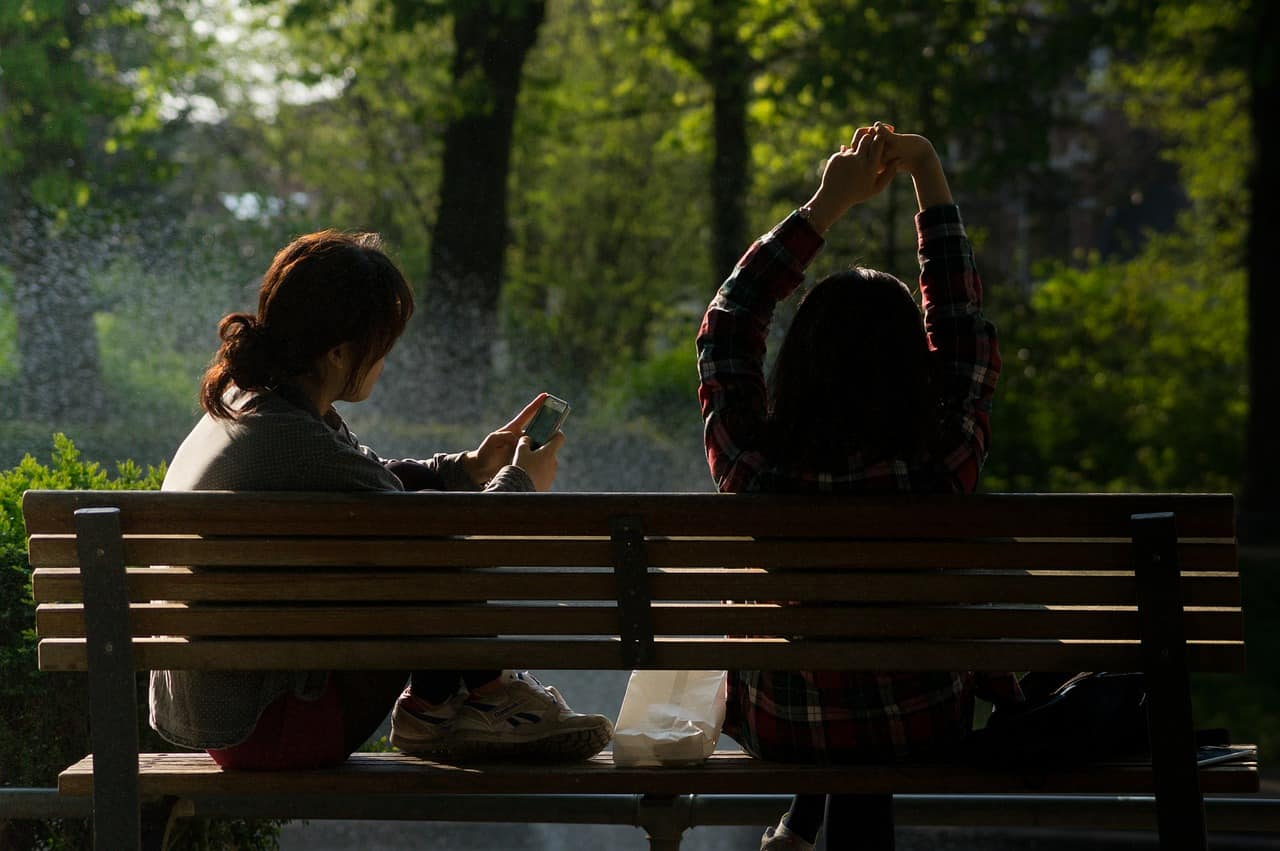 2 girls sitting on an outdoor bench